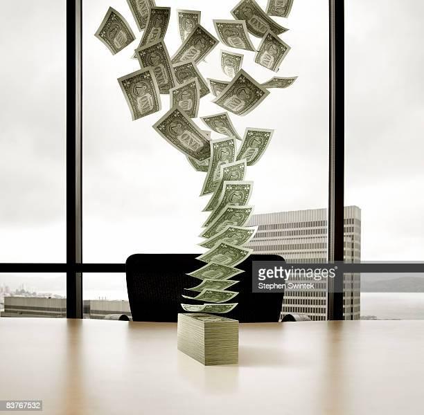 U.S. dollar bills falling onto a desk