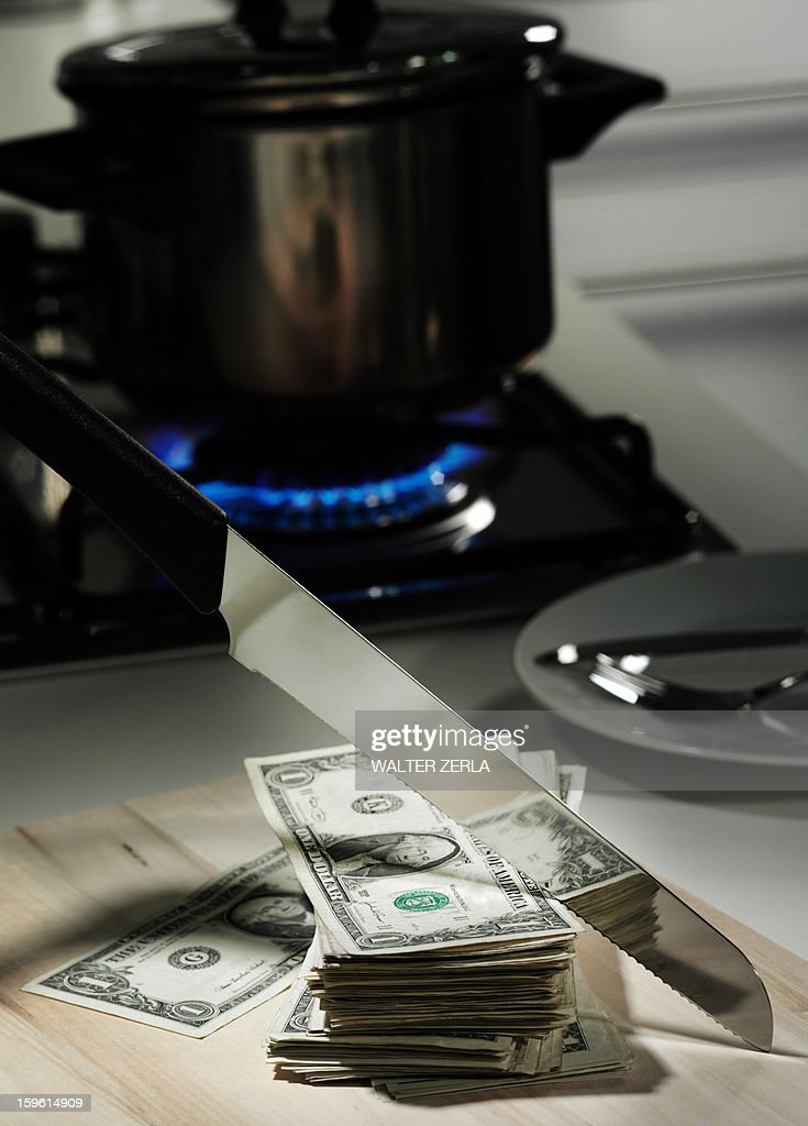 Dollar bills in frying pan on stove : Stock Photo