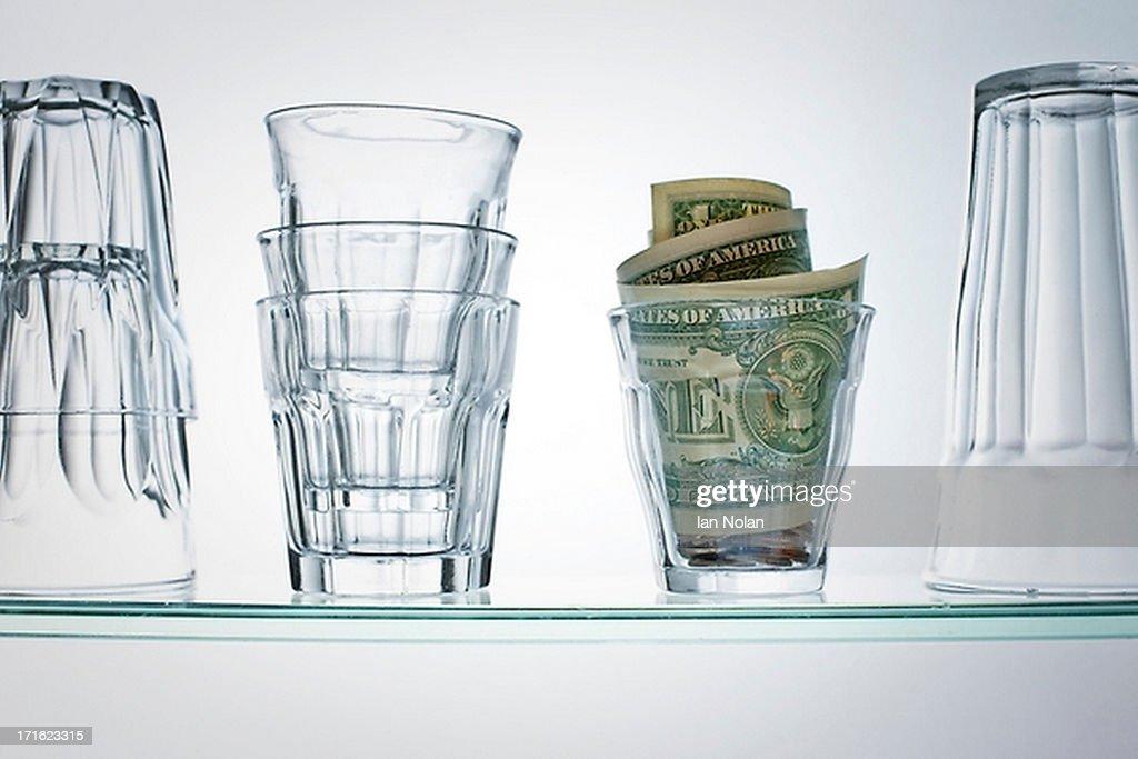 Dollar bills in glass on shelf : Stock Photo