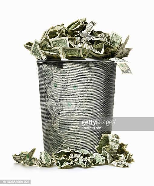 Dollar bills spilling out of wire waste basket