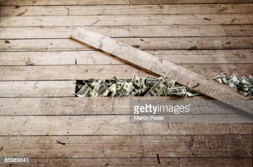 100 dollar bills stashed under a floorboards
