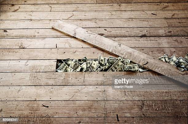 100 dollar bills stashed under a floorboards