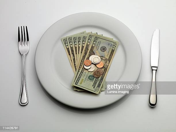 US dollar currency on a dinner plate.
