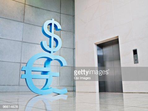 Dollar, euro and British pound symbols near elevator : Stock Photo
