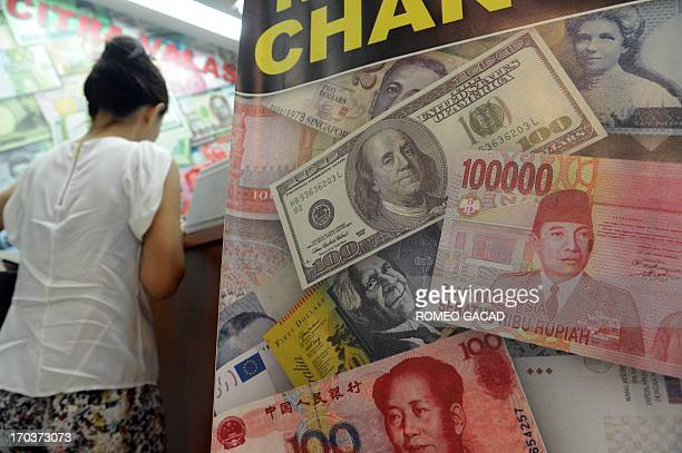 US dollar Indonesian rupiah and Chinese renminbi currencies are displayed in the poster of a money exchange shop in Jakarta on June 12 2013...
