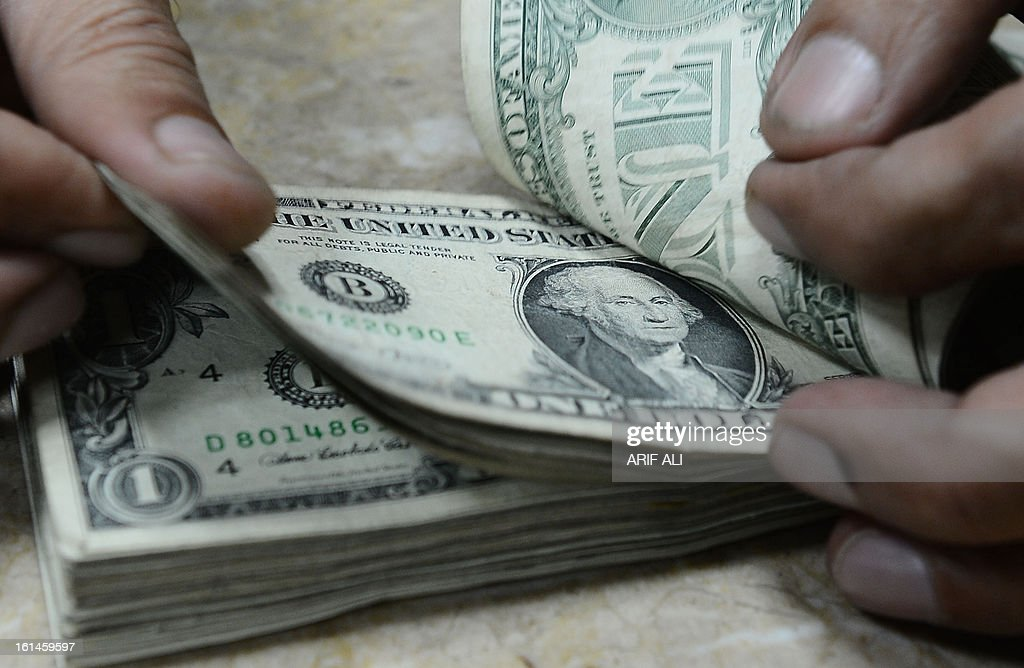 US dollar notes are pictured at a currency exchange shop in Lahore on February 11, 2013. The Pakistani rupee on sank to an all-time low against the US dollar over forex reserve fears as the country repayed USD 146 million to the International Monetary Fund. AFP PHOTO/ Arif ALI