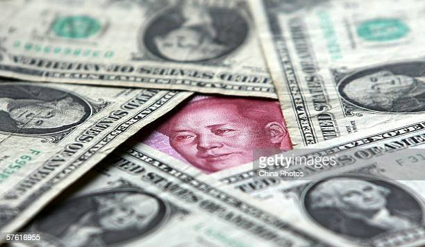 Dollars and yuan notes are seen at a bank on May 15 2006 in Beijing China China's official exchange rate rose today to 79982 yuan per US dollar its...