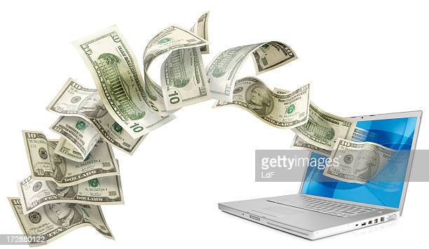 Dollars flying from the screen of an aluminium laptop