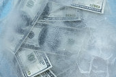 100 dollars frozen melt. Banknotes frozen in ice.