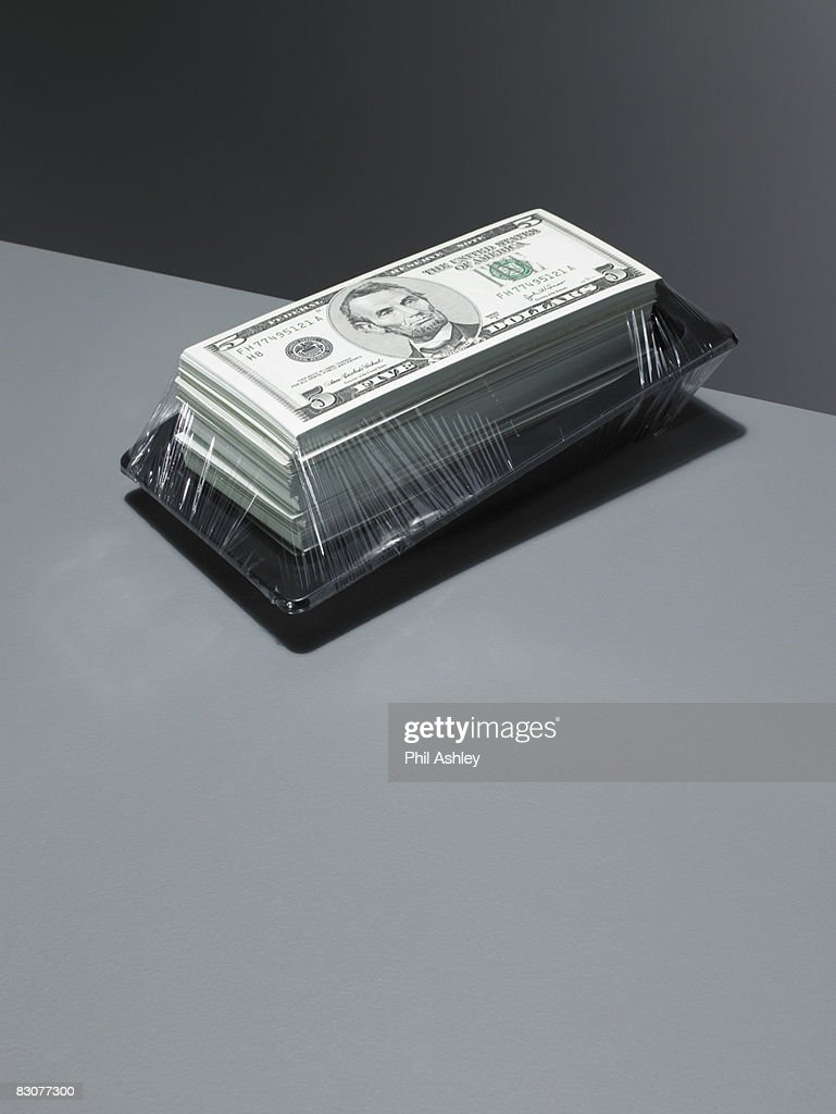 dollars wrapped in cling film on an edge : Stock Photo