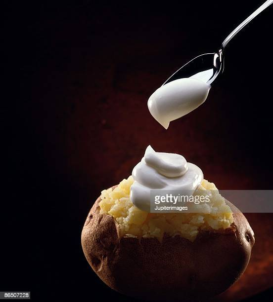 Dollop of sour cream on baked potato