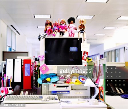 Dolls and stickers on computer monitor in office : Stock Photo