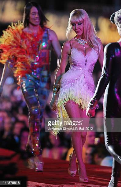 Dolly Buster and model Jorge Gonzalez walk the catwalk during the Italian Vogue fashion show at the Life Ball 2012 AIDS charity fundraiser at City...