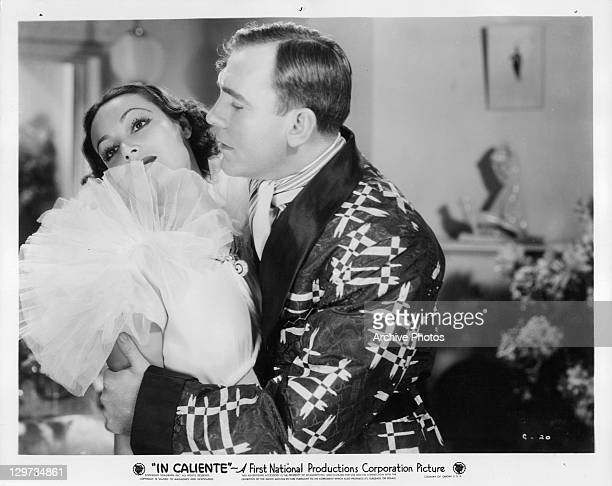 Dolores Del Rio looks away as Pat O'Brien holds her in a scene from the film 'In Caliente' 1935
