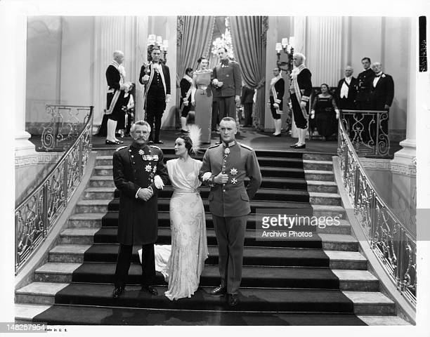 Dolores del Rio wearing an evening gown walking down the stair arm in arm with Maurice Moscovitch and George Sanders in a scene from the film 'Lancer...