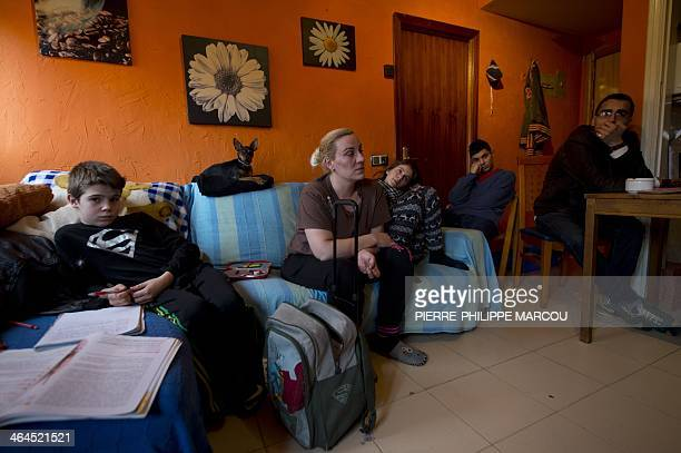 CUENCA Dolores Ferrer sits on her couch beside her daughter Nerea her son Cristian and friends in Madrid on January 21 2014 For two years the life of...