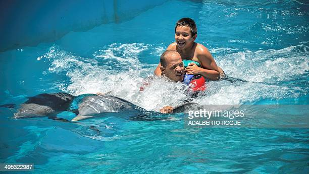 Dolphin trainer Adrian Calderon helps child Dariel Quesada to surf towed by dolphins during a therapy session on May 26 2014 at the National Aquarium...