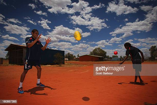 Dom Barry of the Indigenous All Stars plays football with schoolchildren as members of the Indigenous All Stars visit Yuendumu School in the...