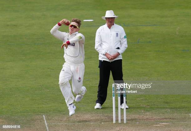 Dom Bess of Somerset bowls as umpire Nick Cook looks on during Day Two of The Specsavers County Championship Division One match between Somerset and...
