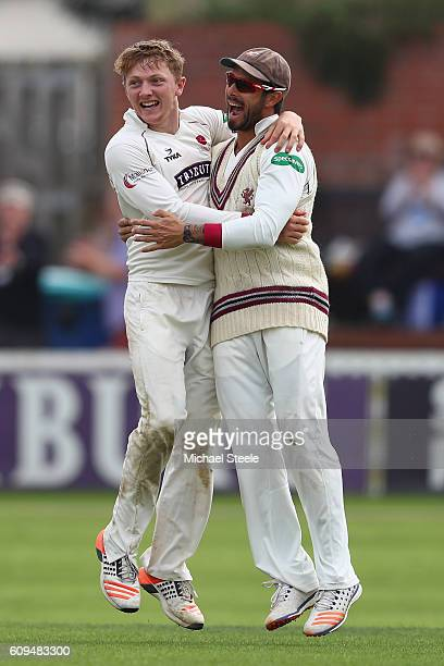 Dom Bess of Somerset celebrates with Peter Trego after claiming the wicket of Michael Lumb caught and bowled during day two of the Specsavers County...