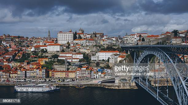 Dom Luis I Bridge Over Douro River Against Cloudy Sky