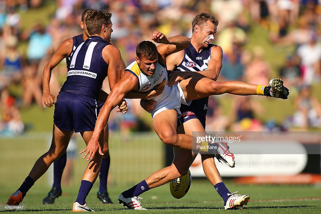 Dom Sheed of the Eagles gets tackled by Paul Duffield of the Dockers during the round two NAB Challenge Cup AFL match between the Fremantle Dockers and the West Coast Eagles at Arena Joondalup on February 18, 2014 in Perth, Australia.