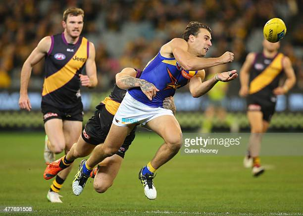 Dom Sheed of the Eagles handballs whilst being tackled by Dustin Martin of the Tigers during the round 12 AFL match between the Richmond Tigers and...