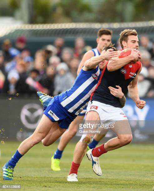 Dom Tyson of the Demons is tackled during the round 19 AFL match between the North Melbourne Kangaroos and the Melbourne Demons at Blundstone Arena...