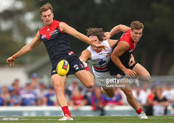 Dom Tyson of the Demons kicks as Jack Viney of the Demons shepherds Marcus Bontempelli of the Bulldogs during the NAB Challenge AFL match between the...
