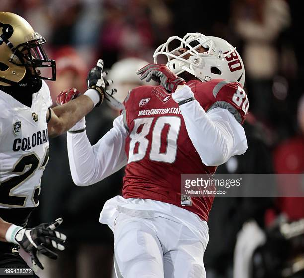 Dom Williams of the Washington State Cougars looks to the ball before catching a pass against Ahkello Witherspoon of the Colorado Buffaloes in the...