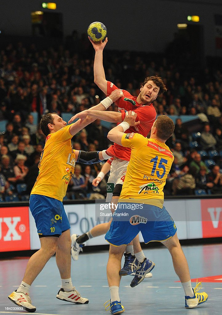 Domago Duvjak of Hamburg is challenged by Aelm Toskic and Vid Poteko of Celje during the hanball Champions League game between HSV Hamburg and Celje...