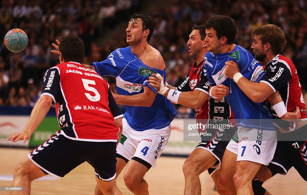 Domagoj Duvnjak (2nd L) of Hamburg is challenged by Tobias Karlsson during the DKB Handball Bundesliga match between HSV Hamburg and SG Flensburg-Handewitt at the O2 World on September 12, 2012 in Hamburg, Germany.