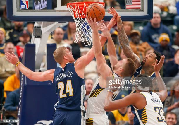 Domantas Sabonis of the Indiana Pacers shoots the ball as Mason Plumlee of the Denver Nuggets and Wilson Chandler of the Denver Nuggets defends at...
