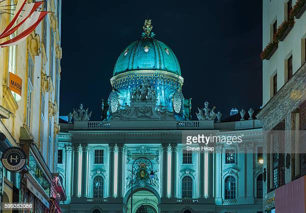 Dome of Hofburg Palace at night illuminated in blue with shops on Kohlmarkt framing view in Vienna, Austria