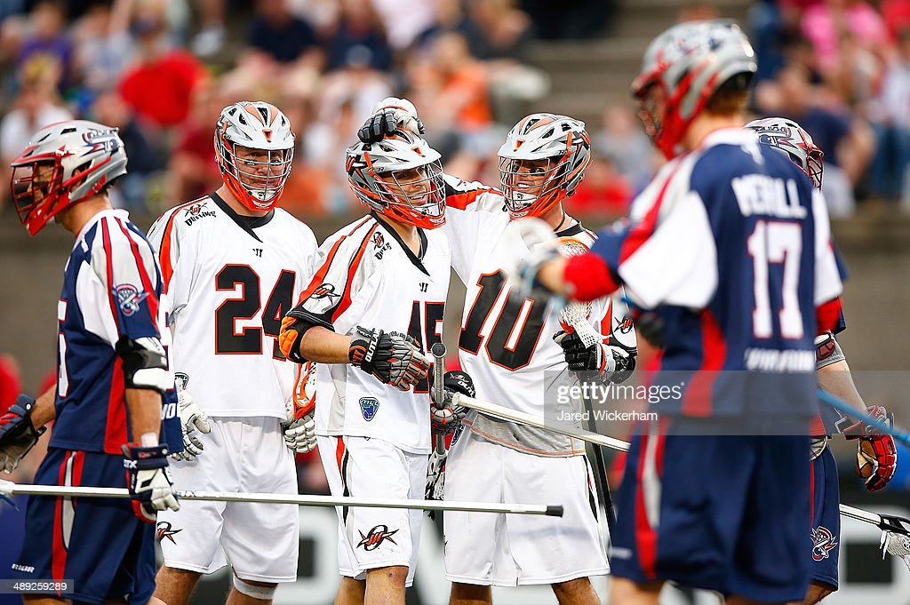 Domenic Sebestiani #45 of the Denver Outlaws is congratulated on his goal by teammates in the first half against the Boston Cannons at Harvard Stadium on May 10, 2014 in Boston, Massachusetts.