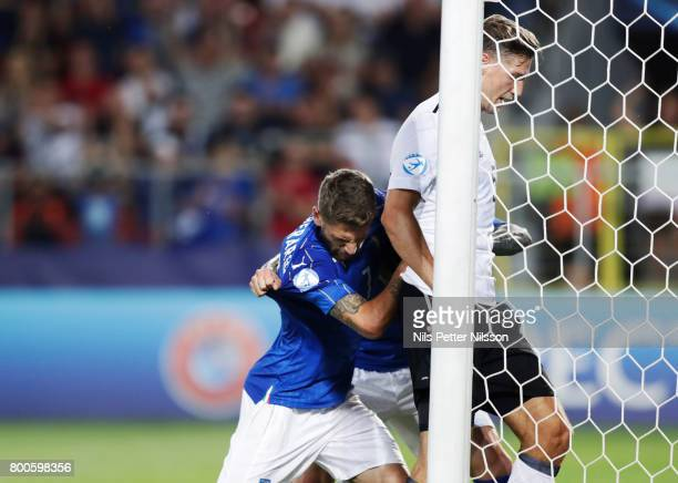 Domenico Berardi and Federico Bernardeschi of Italy pushes Niklas Stark of Germany into the goal during the UEFA U21 championship match between Italy...