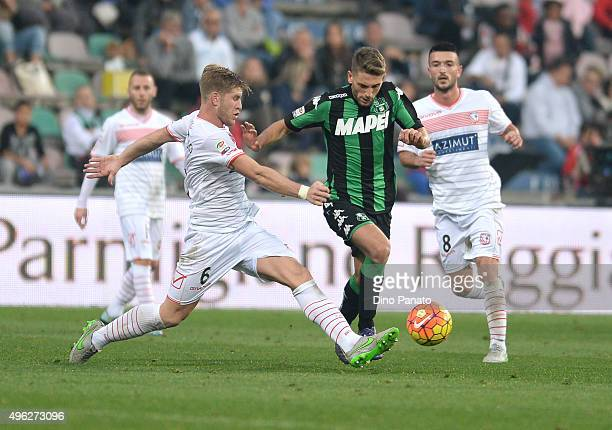 Domenico Berardi of Sassuolo Calcio competes with Riccardo Gagliolo and Raffaele Bianco of Carpi FC during the Serie A match between US Sassuolo...