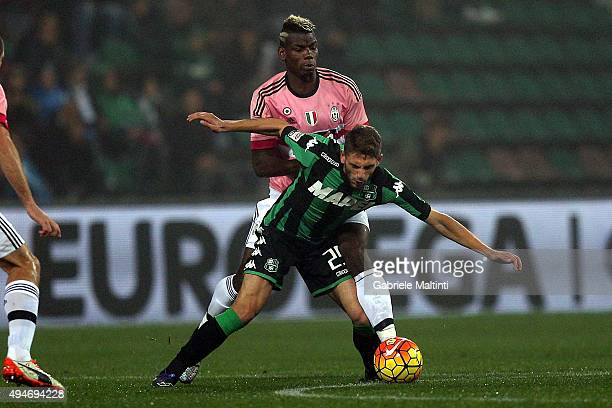 Domenico Berardi of US Sassuolo Calcio battles for the ball with Paul Pogba of Juventus FC during the Serie A match between US Sassuolo Calcio and...