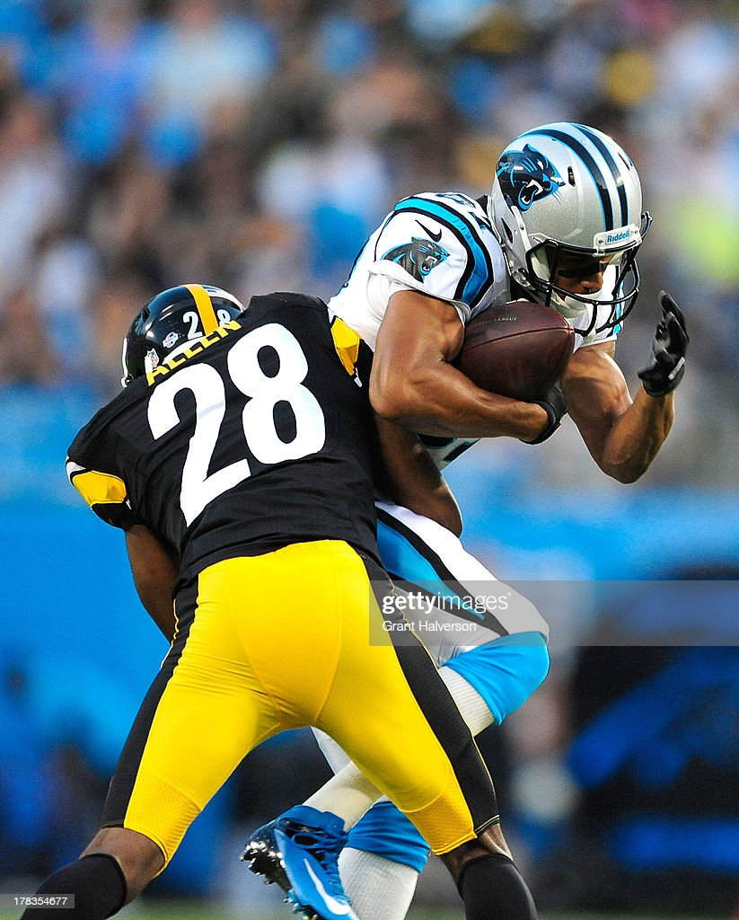 Domenik Hixon #87 of the Carolina Panthers makes a catch under pressure from Cortez Allen #28 of the Pittsburgh Steelers during a preseason NFL game at Bank of America Stadium on August 29, 2013 in Charlotte, North Carolina.