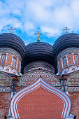 Domes with crosses of an old orthodox church against a blue sky with clouds