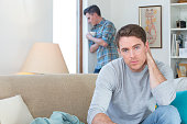 A young gay couple are at opposite ends of their living room giving each other the silent treatment. One man is in the foreground with his arms up by his shoulder as the other is standing in the backg