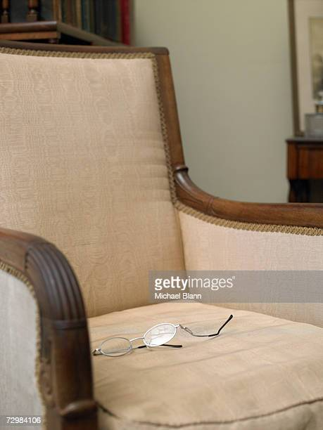 Domestic armchair with damaged spectacles on cushion