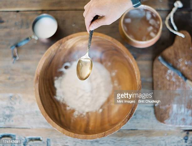 A domestic kitchen. A cook preparing a meal. A large bowl with oil and flour. Creating pastry.