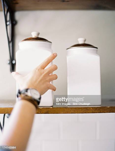 A domestic kitchen. A person reaching up to two storage jars on a shelf.