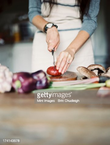 A domestic kitchen. A table top. Young woman chopping fresh vegetables with a knife.