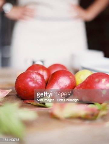 A domestic kitchen tabletop. A small group of fresh organic pears and a stack of white plates. : Stock Photo