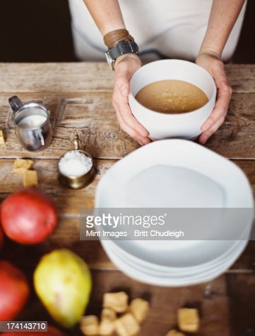 A domestic kitchen tabletop. A stack of white plates and fresh pears and a stack of sugar cubes. A bowl of  fudge sauce. : Foto stock