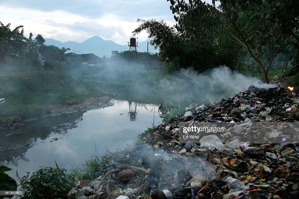 Domestic waste burns on the banks of the heavily polluted Citarum river near the town of Majalaya, a major textile producer on November 7, 2013 in Majalaya, Indonesia. The effects of domestic and industrial waste from factories along the river have prompted two leading environmental groups, Green Cross of Switzerland and the Blacksmith Institute, to name the Citarum river as one of the earth's 10 most polluted places in their annual report.