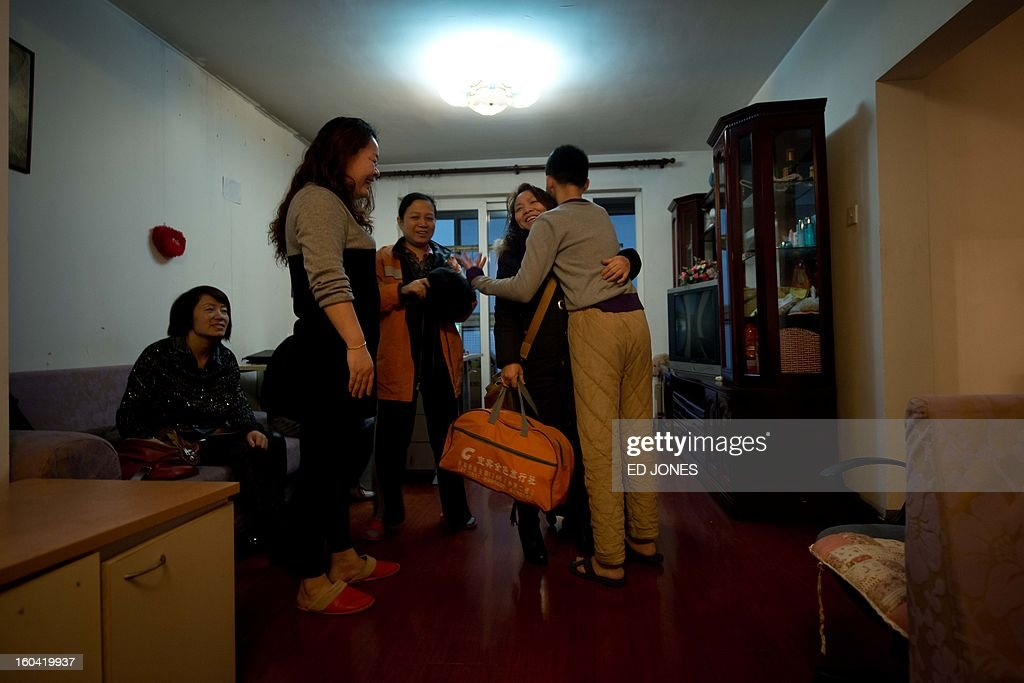 Domestic worker Chen Guolan (C) says goodbye as she prepares to leave the apartment of her employers, where she also lives, in Beijing on January 31, 2013 to catch a train bound for the south-western Chinese city of Chongqing, a journey of 32 hours, and where she will also take another train for a further 6 hours to reach her home in Yiban, Sichuan province. The world's largest annual migration is underway in China with tens of thousands in the capital boarding trains to journey home for Lunar New Year celebrations. Passengers will log 220 million train rides during the 40-day travel season as they criss-cross the country to celebrate with their families on February 10, but just as making the trip home can be laborious -- often lasting one or two days -- so can simply acquiring a seat on the train, and every year complaints arise about the inefficiency or unfairness of the system, although an initiative allowing travelers to purchase tickets online aims to curb long queuing times. AFP PHOTO / Ed Jones