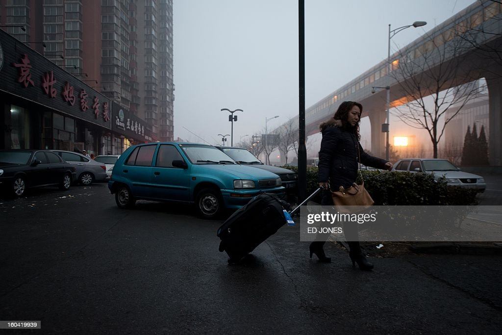 Domestic worker Chen Guolan walks to a bus stop after leaving the apartment of her employers, where she also lives, in Beijing on January 31, 2013 to catch a train bound for the south-western Chinese city of Chongqing, a journey of 32 hours, and where she will also take another train for a further 6 hours to reach her home in Yiban, Sichuan province. The world's largest annual migration is underway in China with tens of thousands in the capital boarding trains to journey home for Lunar New Year celebrations. Passengers will log 220 million train rides during the 40-day travel season as they criss-cross the country to celebrate with their families on February 10, but just as making the trip home can be laborious -- often lasting one or two days -- so can simply acquiring a seat on the train, and every year complaints arise about the inefficiency or unfairness of the system, although an initiative allowing travelers to purchase tickets online aims to curb long queuing times. AFP PHOTO / Ed Jones